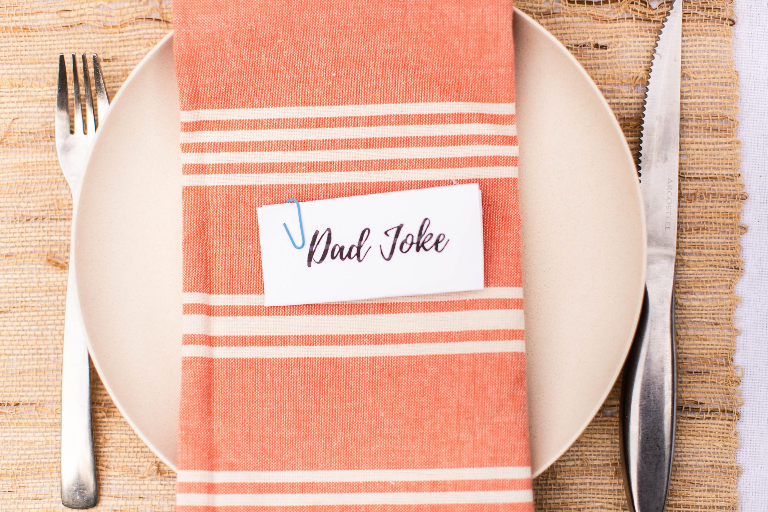 table setting for Father's Day. Bamboo plate, Dad Joke on piece of paper, coral striped dinner napkin