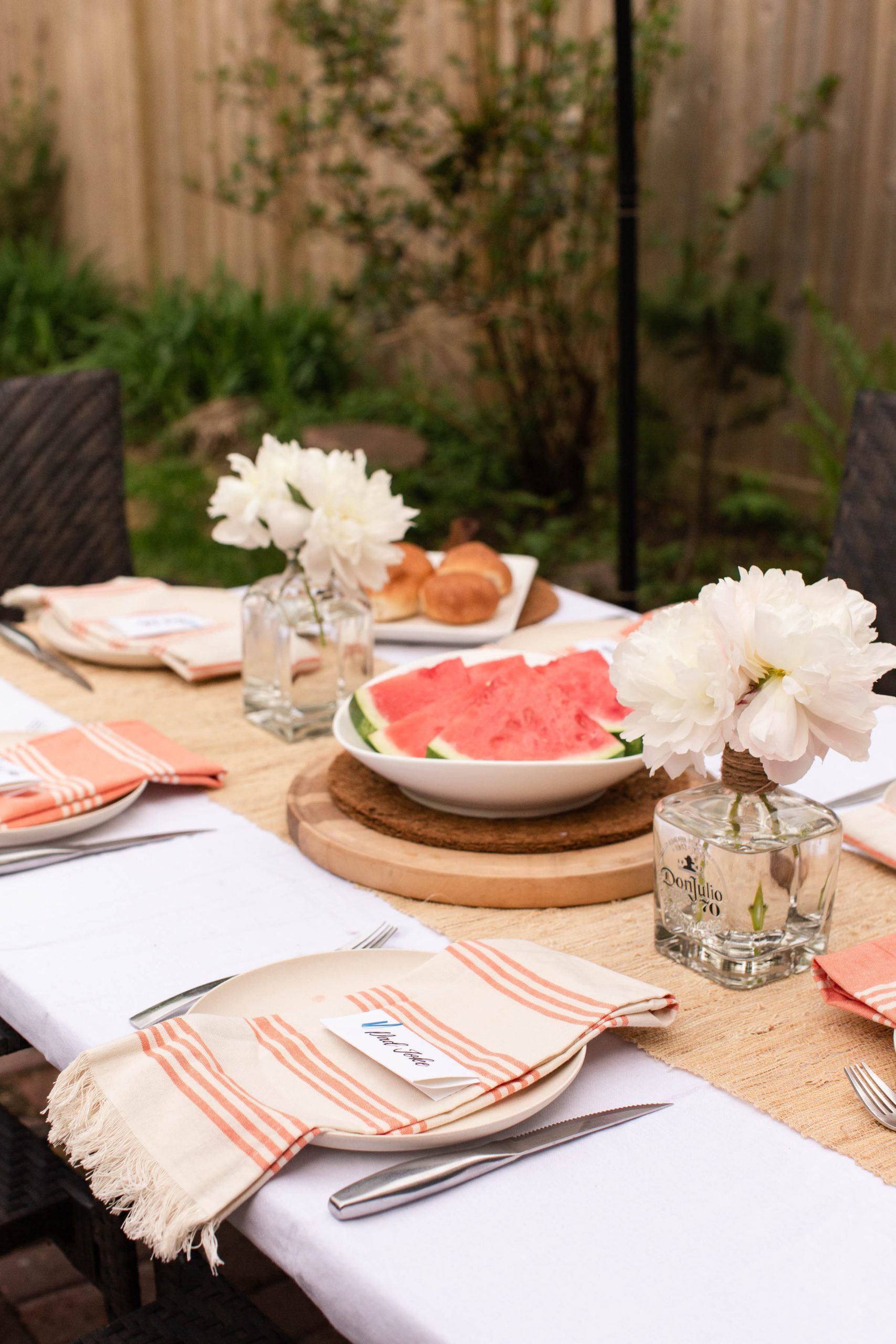 coral and cream tablescape with buns and watermelon. Peonies in old tequila and scotch bottles-3
