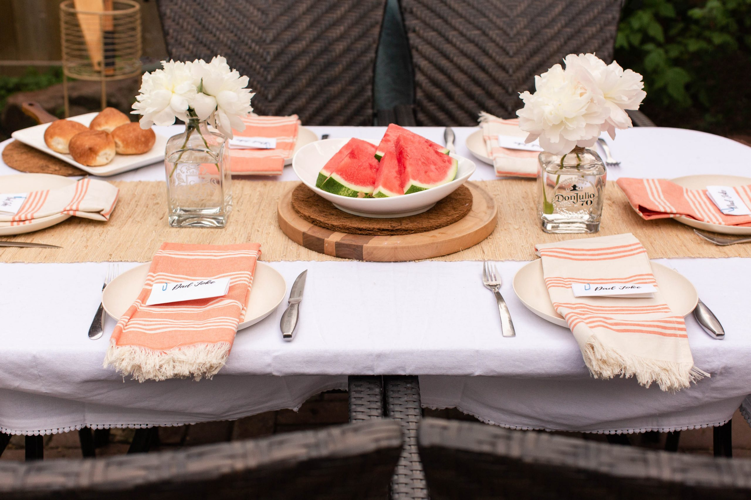 coral and cream tablescape with buns and watermelon. Peonies in old tequila and scotch bottles-2