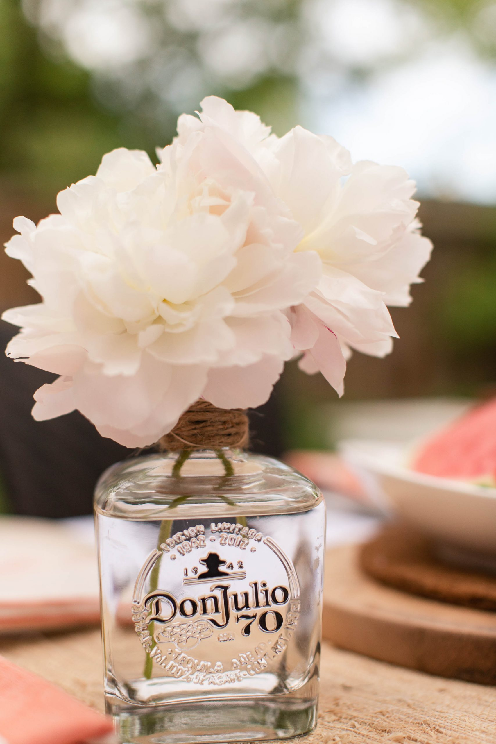 white peonies in old tequila bottle vase