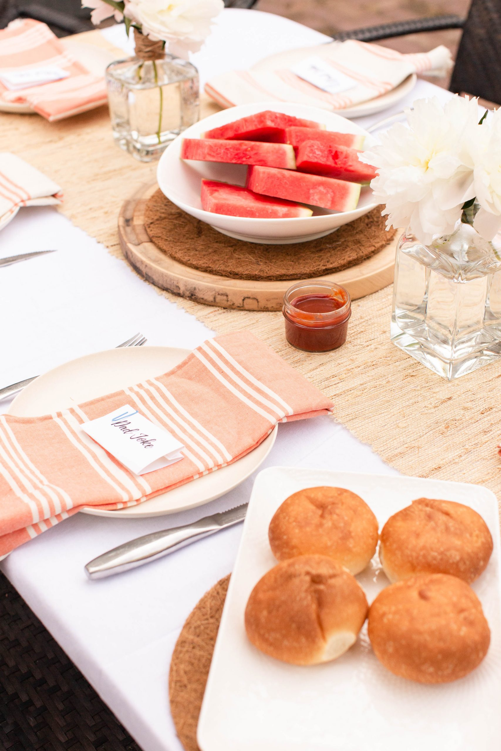 coral and cream tablescape with buns and watermelon. Peonies in old tequila and scotch bottles